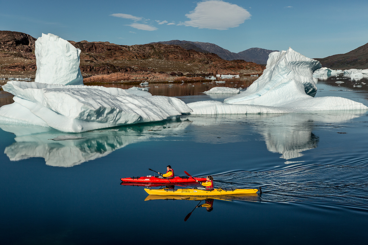 Two kayakers passing icebergs in Sermilik fjord near Tasiusaq sheep farm in South Greenland.jpg