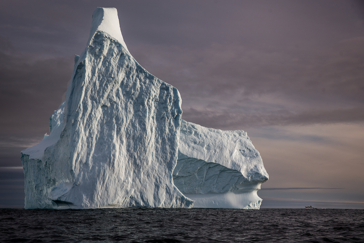 A huge iceberg and a tiny boat near Tasiilaq in East Greenland.jpg