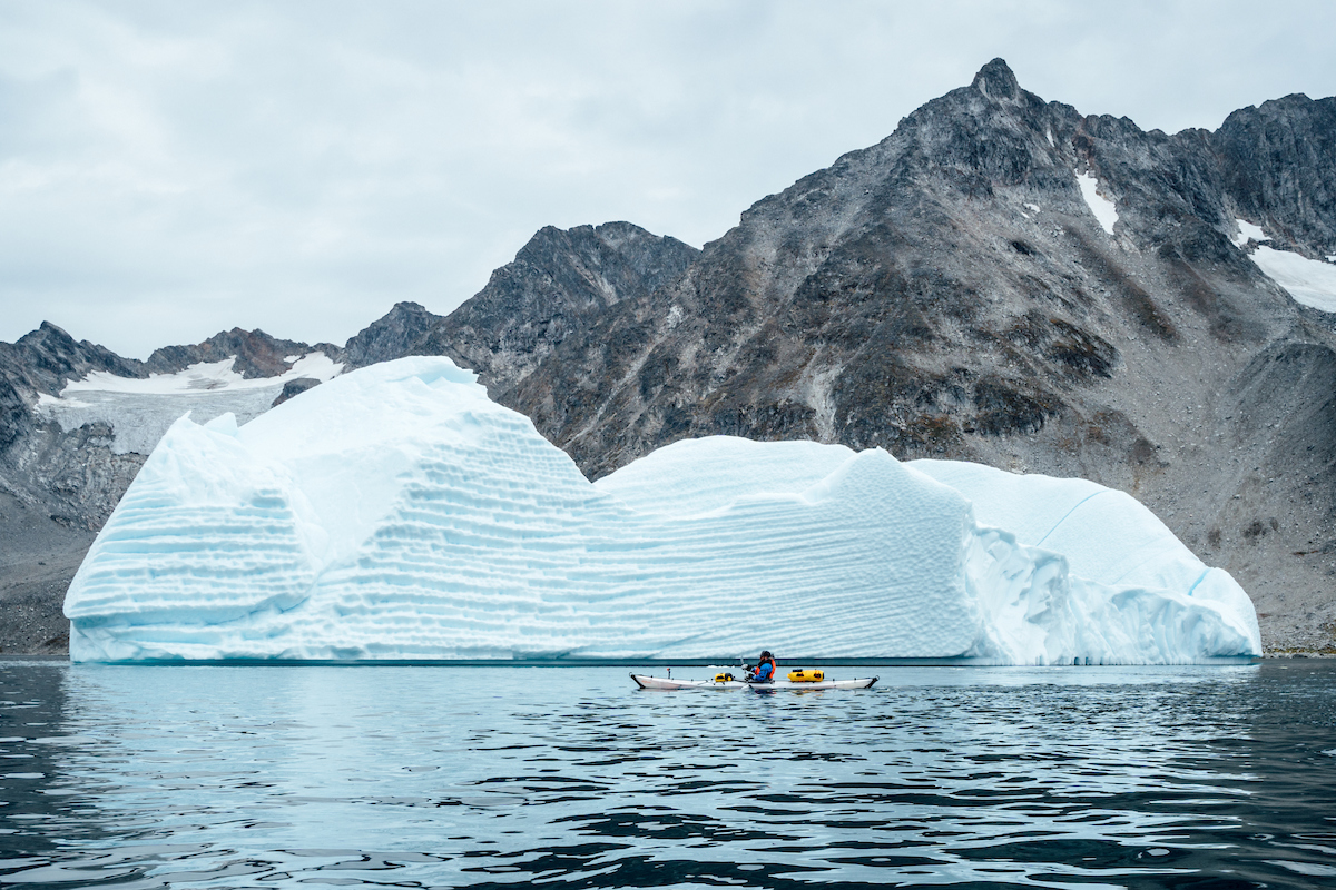 A kayaker paddles alongside an iceberg, Just North Of Kuummiut.jpg